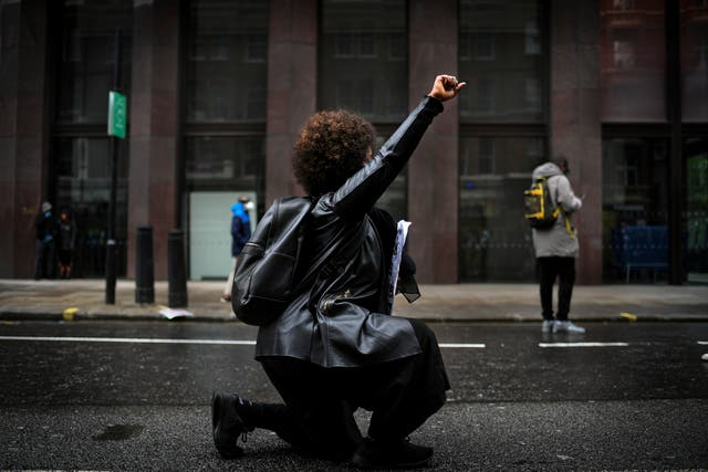 A woman kneels during a Black Lives Matter rally in London