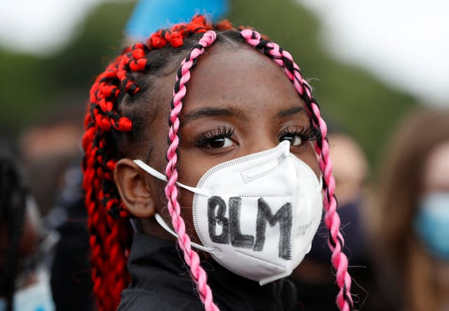 A demonstrator is seen with a protective face mask during a Black Lives Matter protest in Watford