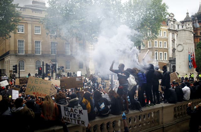 Demonstrators with a flare are seen during a Black Lives Matter protest near Downing street in London