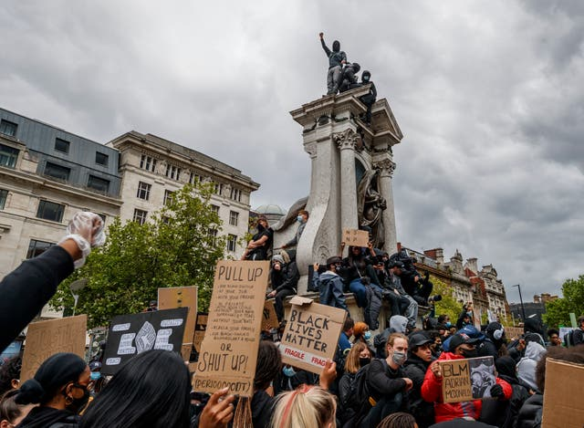 People climbing on top of the Queen Victoria Statue as they take part in a Black Lives Matter protest rally in Manchester Piccadilly Gardens