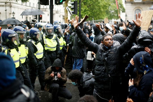 Demonstrators are seen as police officers look on during a Black Lives Matter protest near Downing street in London