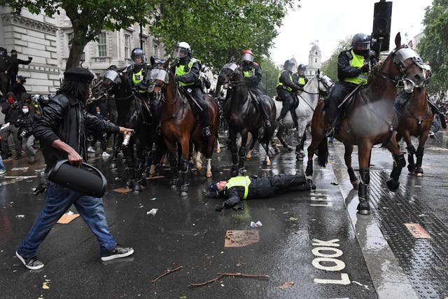 A demonstrator points towards a mounted police officer laying in the road after being unseated from their horse, during a demonstration on Whitehall, near the entrance to Downing Street