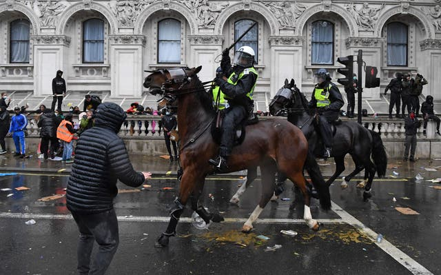 A mounted police officer raises their baton as police horses ride along Whitehall, past the entrance to Downing Street, in an attempt to disperse protestors gathered in central London