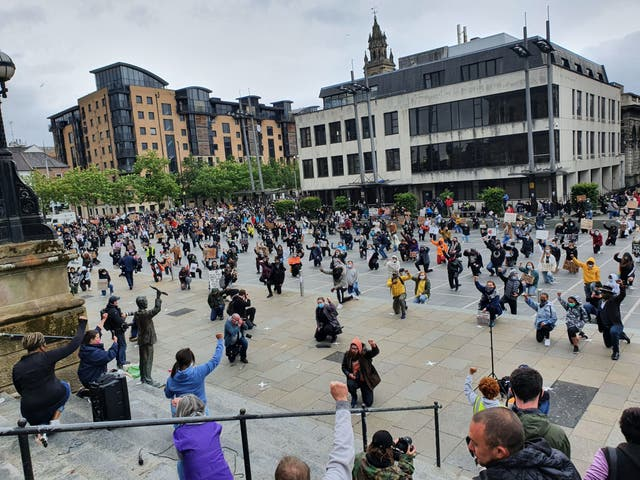 People take part in a Black Lives Matter protest rally in Custom House Square, Belfast