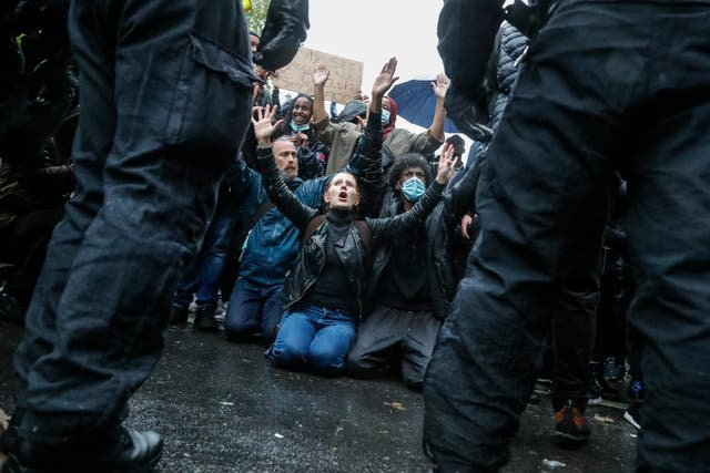 Demonstrators kneel facing police officers after scuffles during a Black Lives Matter march in London
