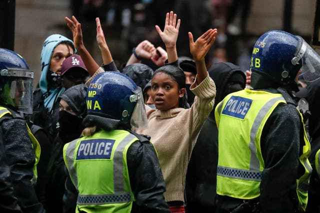 Demonstrators raise their hands facing police officers after scuffles during a Black Lives Matter march in London