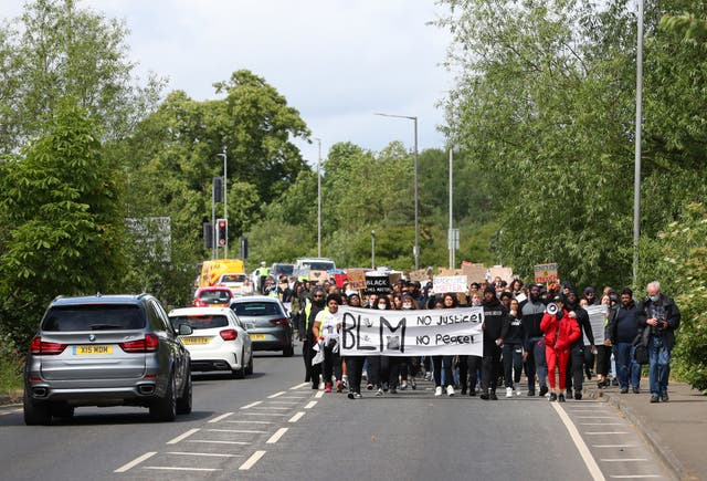 Protesters hold up signs as they march along a road during a peaceful Black Lives Matter march in Aylesbury