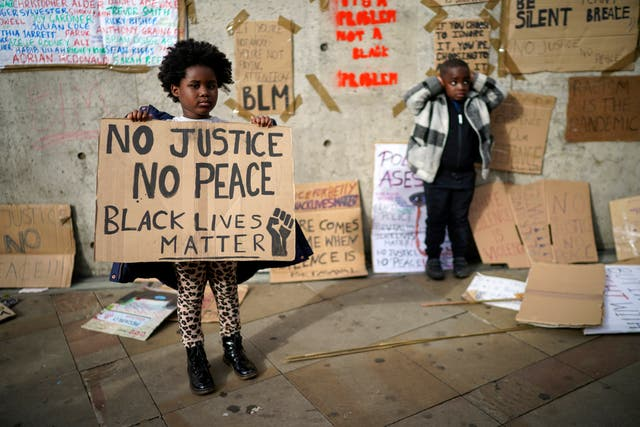 Children pose for their family in front of discarded placards fixed on a wall in Piccadilly Gardens after a Black Lives Matter demonstrations in Manchester