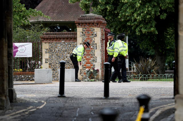 Police officers place flowers left by people outside the police cordon nearer the scene of multiple stabbings in Reading, Bretagne, juin 21,