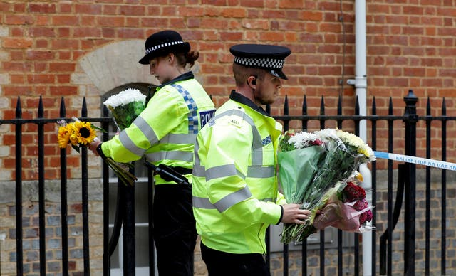 Police officers carry flowers left by people next to the police cordon at the scene of multiple stabbings in Reading, Bretagne, juin 21, 2020.