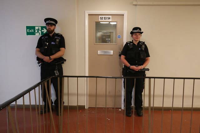 Police officers standing guard outside the corridor of a top-floor flat in Basingstoke Road, En train de lire, where the suspect in the Forbury Gardens stabbings was detained. The suspect in the Reading stabbings is a Libyan asylum seeker and mental health is being considered a major factor in the incident, a security source has told the PA news agency. PA Photo. Picture date: Sunday June 21, 2020.