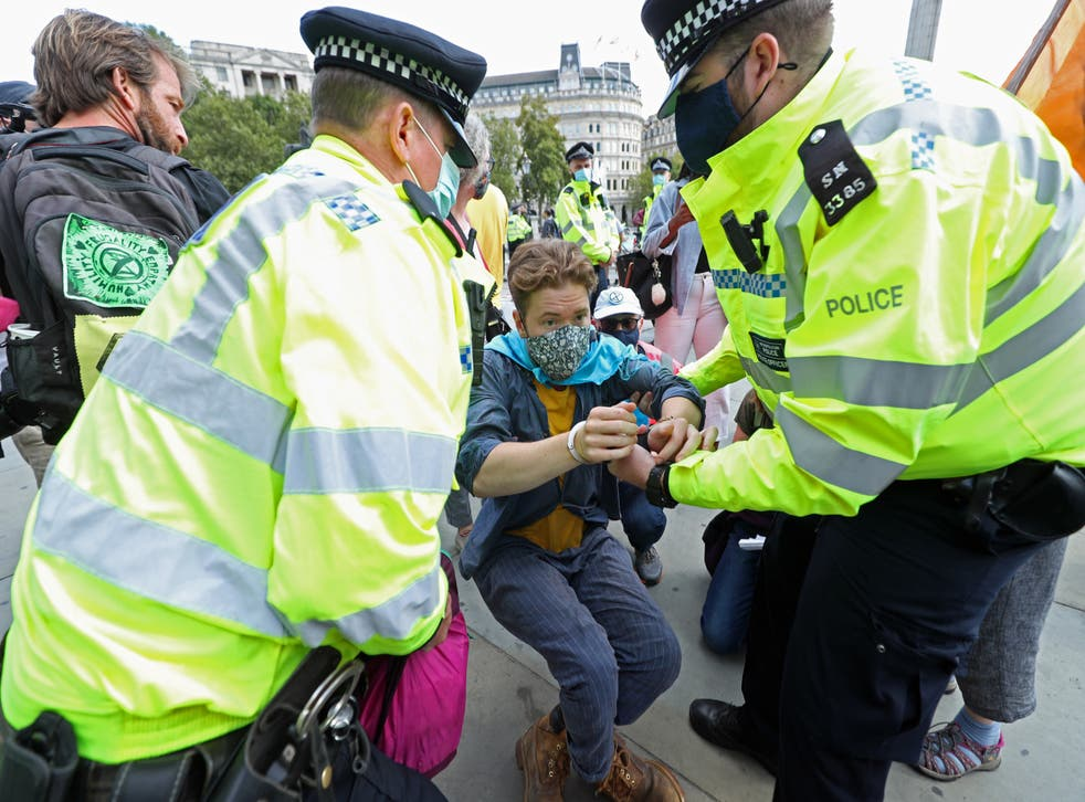 A protester is removed by police officers during an Extinction Rebellion protest in Trafalgar Square, London