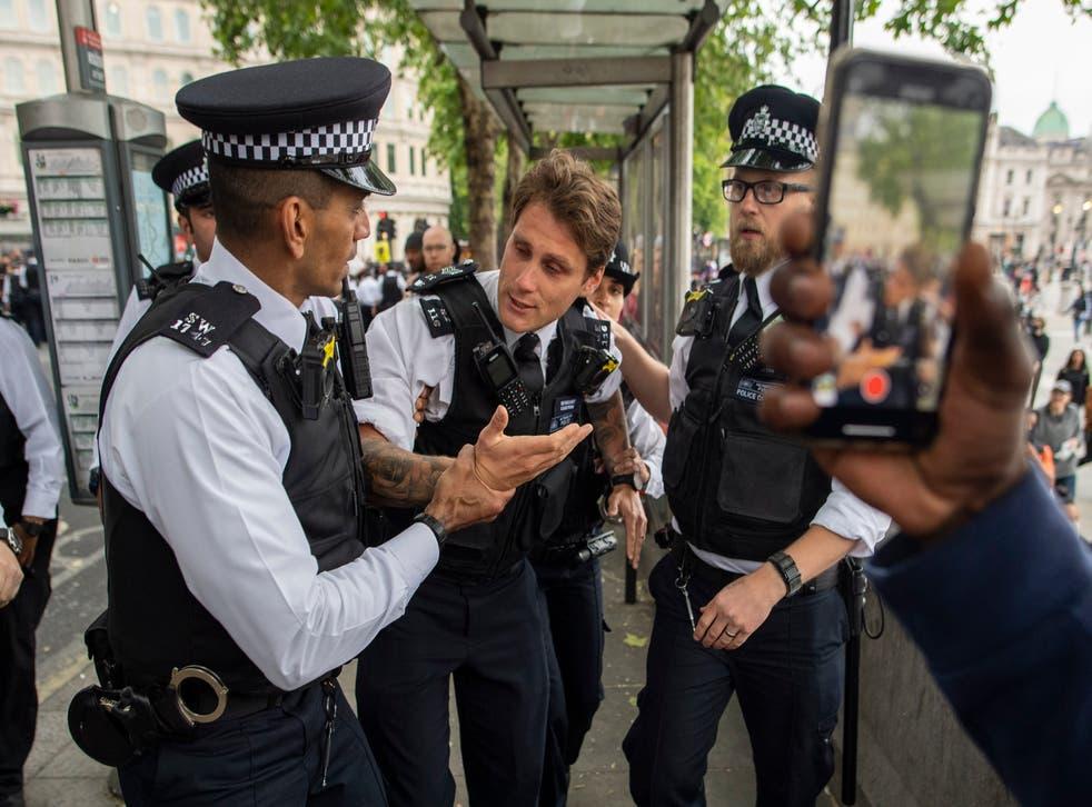 Un oficial de policía herido es asistido por sus colegas durante una protesta en Londres