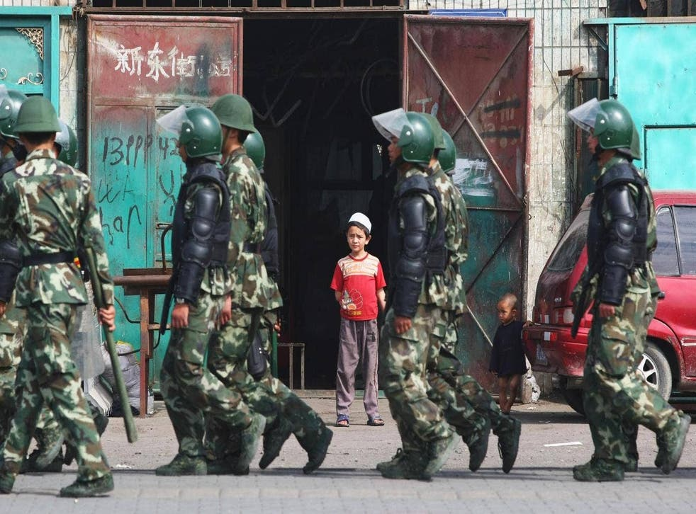 Uighur children watch as police officers pass their home in Urumqi, the capital of Xinjiang