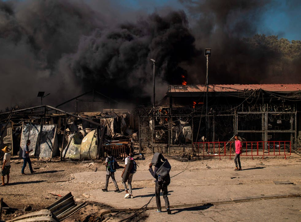 People walk past a fire raging in the camp of Moria on the island of Lesbos
