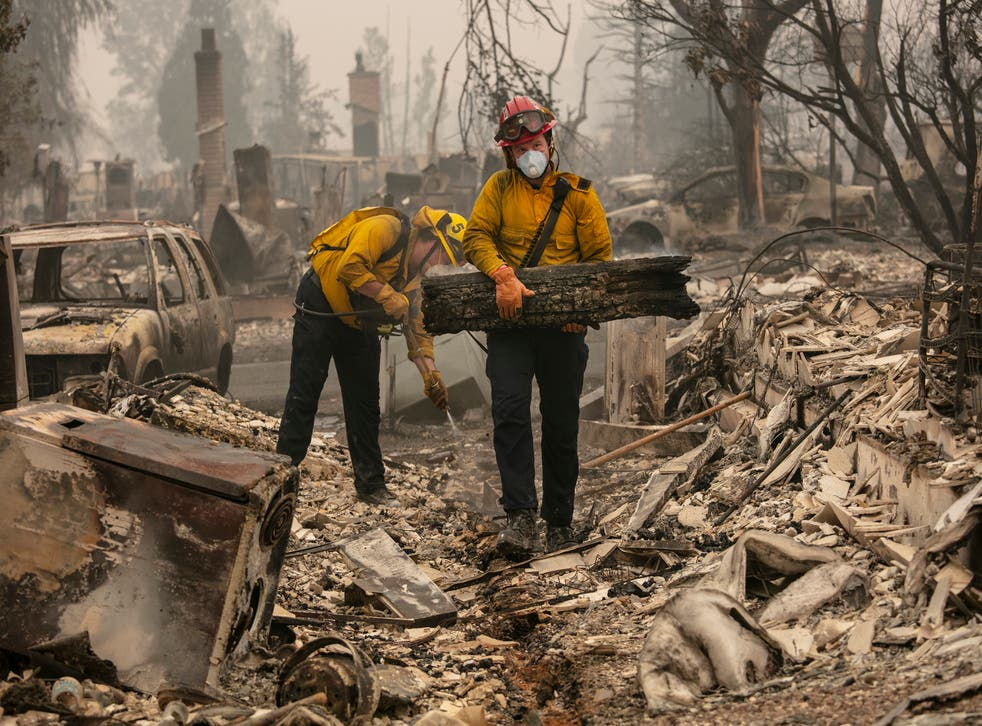 Jackson County District 5 firefighter Captain Aaron Bustard, right, and Andy Buckingham work on a smouldering fire in a burned neighbourhood as destructive wildfires devastate the region on Friday