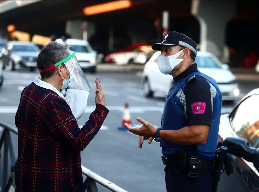 Un policía local habla con una mujer durante el primer día de cierre parcial en Madrid