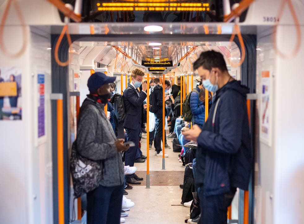 Commuters on board a London Overground train after Prime Minister Boris Johnson announced a range of new restrictions to combat the rise in coronavirus cases in England
