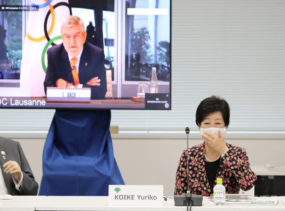 La gobernadora de Tokio, Yuriko Koike, reacciona junto a una pantalla que muestra al presidente del Comité Olímpico Internacional (COI), Thomas Bach, durante una reunión en video de la Comisión de Coordinación del COI para los Juegos Olímpicos de Tokio.