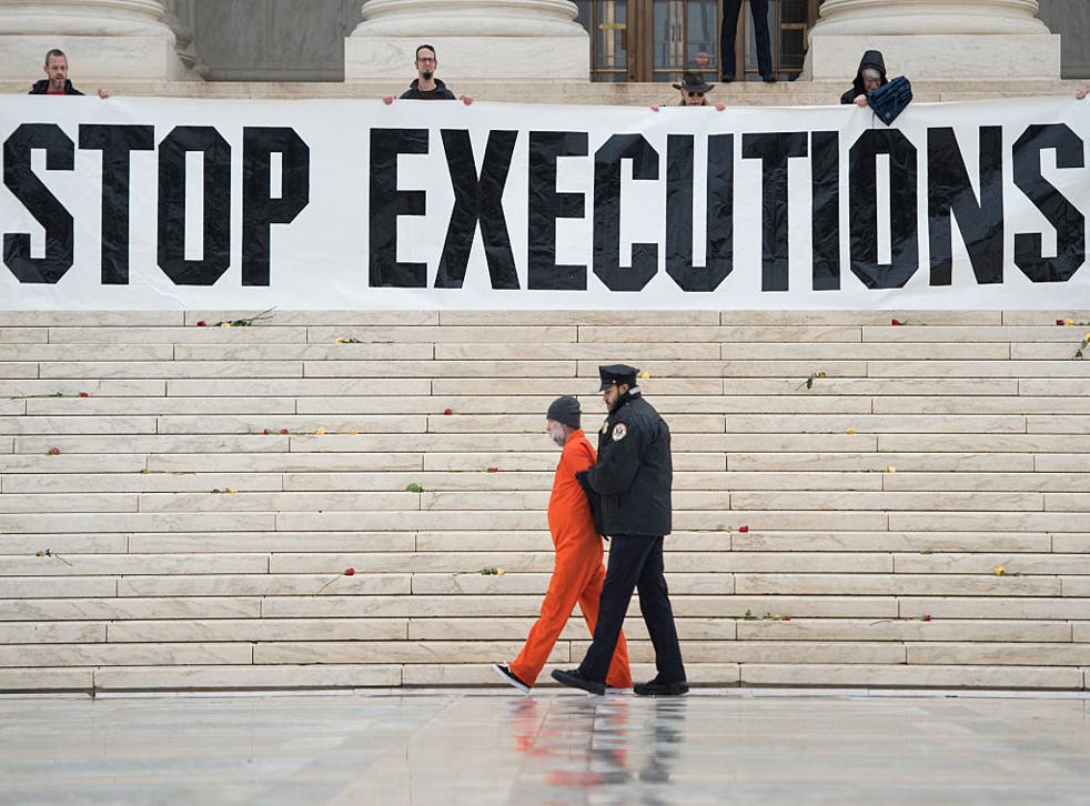 <p>Randy Gardner is removed by police while wearing his executed brother's prison jumpsuit during a protest against the death penalty at the US Supreme Court</p>