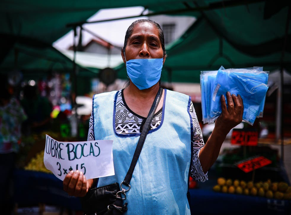 Mujer vende cubrebocas en México durante pandemia por coronavirus.