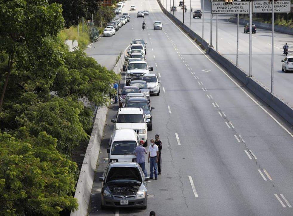 Varias personas se paran junto a vehículos alineados para ingresar a una estación de servicio durante una escasez de combustible en Venezuela.