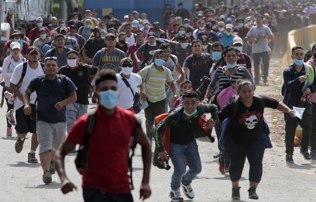 Unos migrantes tratan de cruzar la frontera desde Corinto, Honduras, hacia Corinto, Guatemala, el jueves 1 de octubre de 2020.