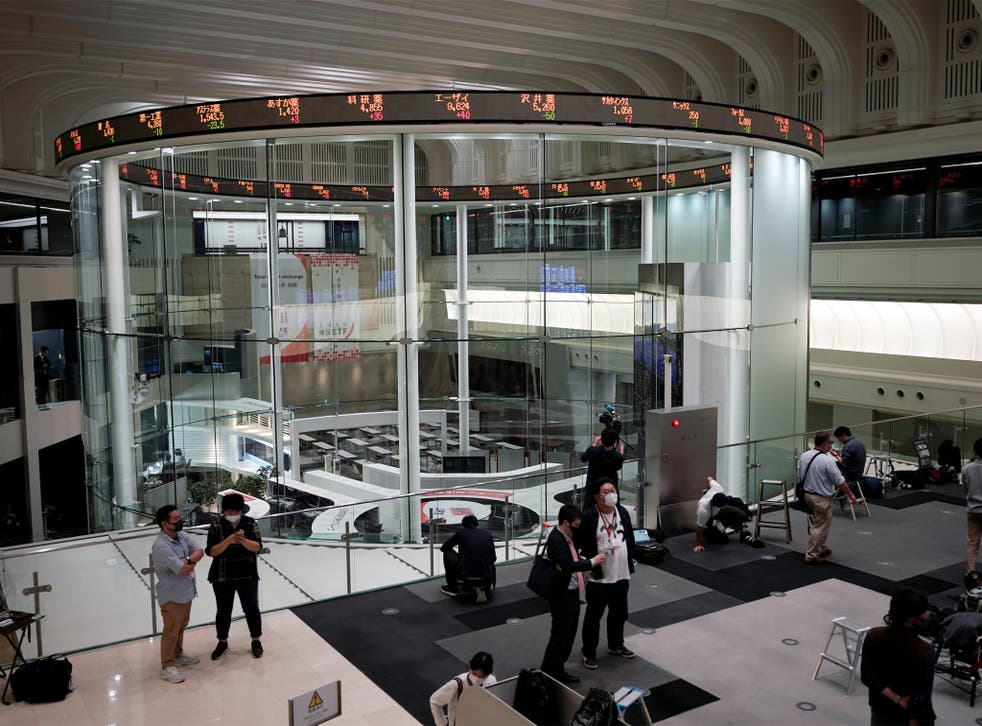 Journalists film an electronic stock board showing reopened Japan's Nikkei 225 index at Tokyo Stock Exchange in Tokyo Friday, Oct. 2, 2020. Tokyo's market resumed trading Friday after a full-day outage due to a malfunction in its computer systems