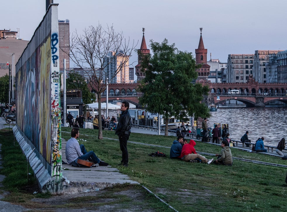 Visitors next to a remaining section of the Berlin Wall at the East Side Gallery