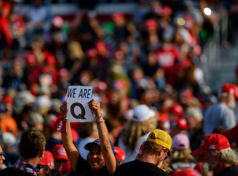 A woman holds up a QAnon sign to the media as attendees wait for President Donald Trump to speak at a campaign rally