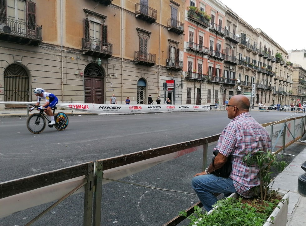 A man sits and watches the riders roar past on Stage 1 of the Giro d'Italia 2020