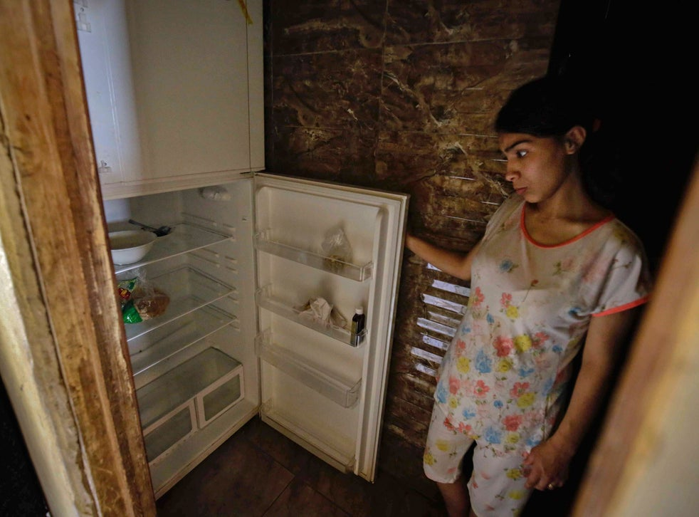 A Lebanese woman next to her empty refrigerator in her apartment in Tripoli