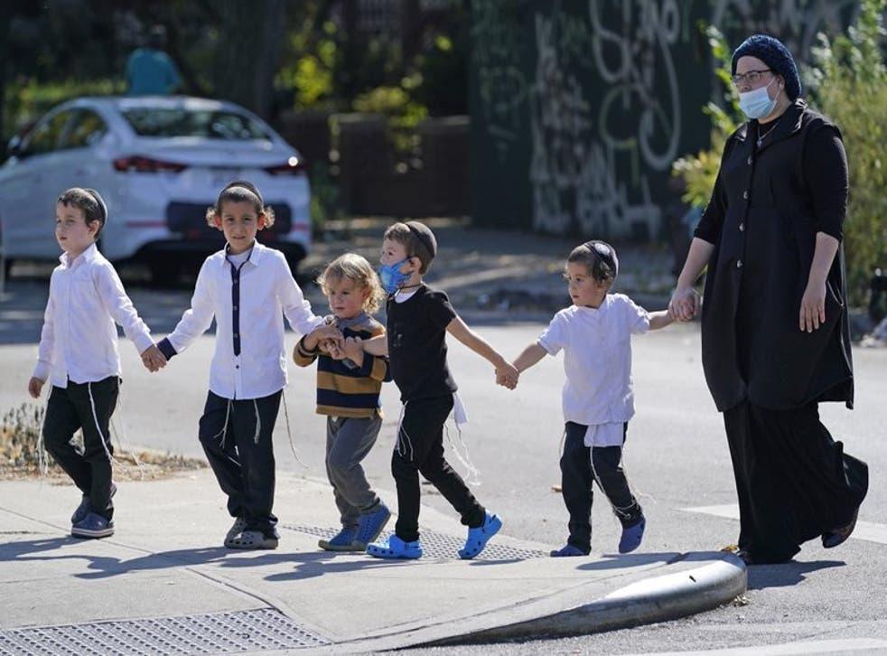 Una mujer con mascarilla por la pandemia de coronavirus y varios niños cruzan una concurrida calle en el vecindario de Midwood, distrito de Brooklyn, en la Ciudad de Nueva York. (Foto/Kathy Willens, Archivo)