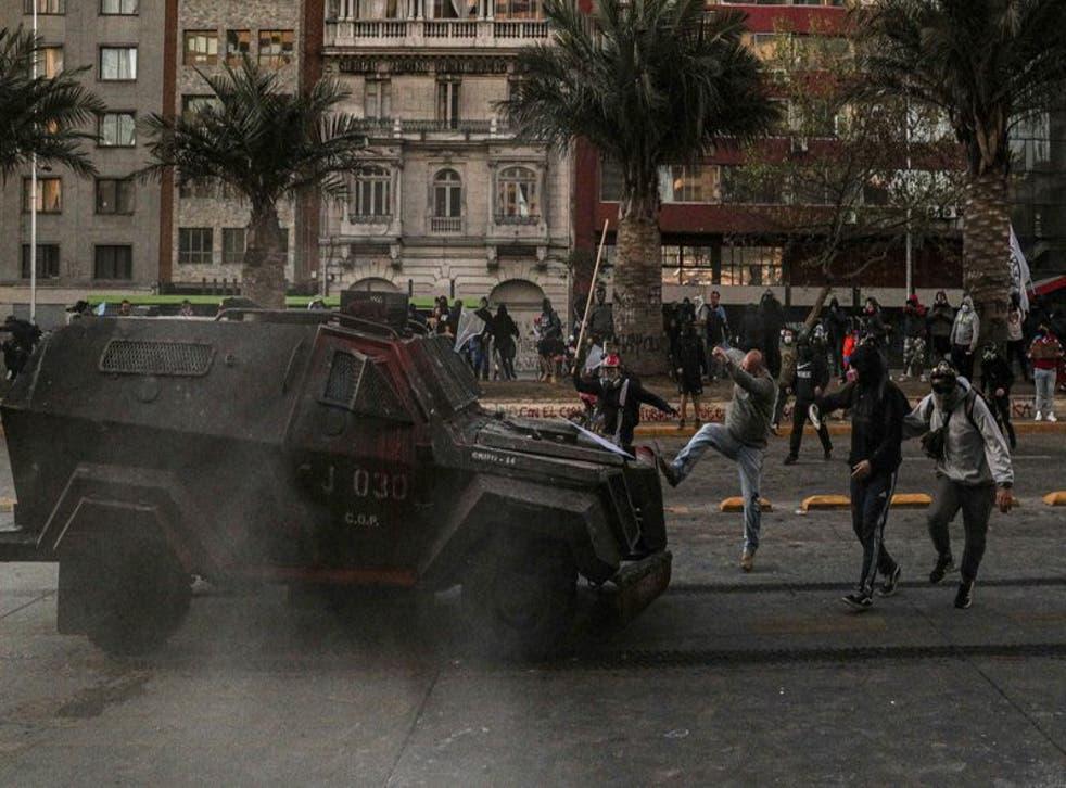 Un manifestante enfrenta un vehículo blindado de la policía durante una protesta contra la brutalidad policial, en Santiago, Chile, el sábado 3 de octubre de 2020. (Foto/Esteban Félix)