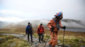 Veteran fundraiser Lloyd Scott, who is attempting to climb the Three Peaks whilst wearing a deep sea diving suit, is followed by members of his support team during his challenge on Ben Nevis in Scotland