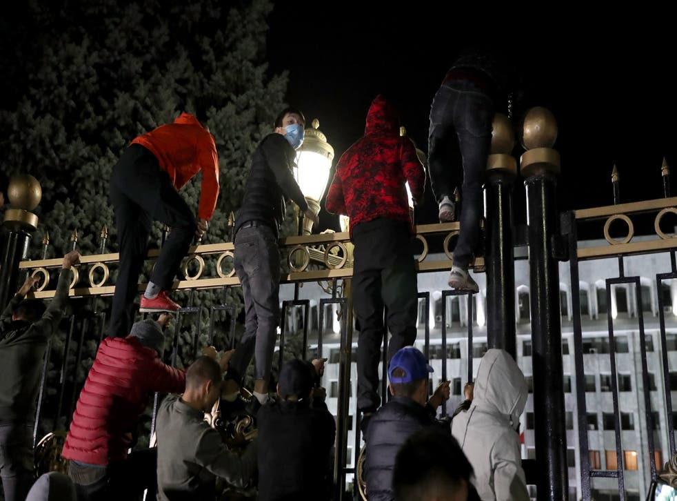 Opposition protesters storm the gates of the parliamentary building, known as the 'White House', in Bishkek
