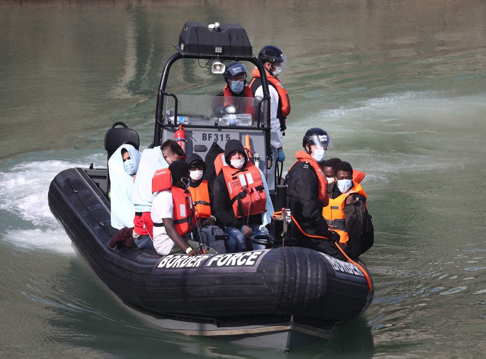 Border Force officers bring migrants from a small boat to shore at Dover
