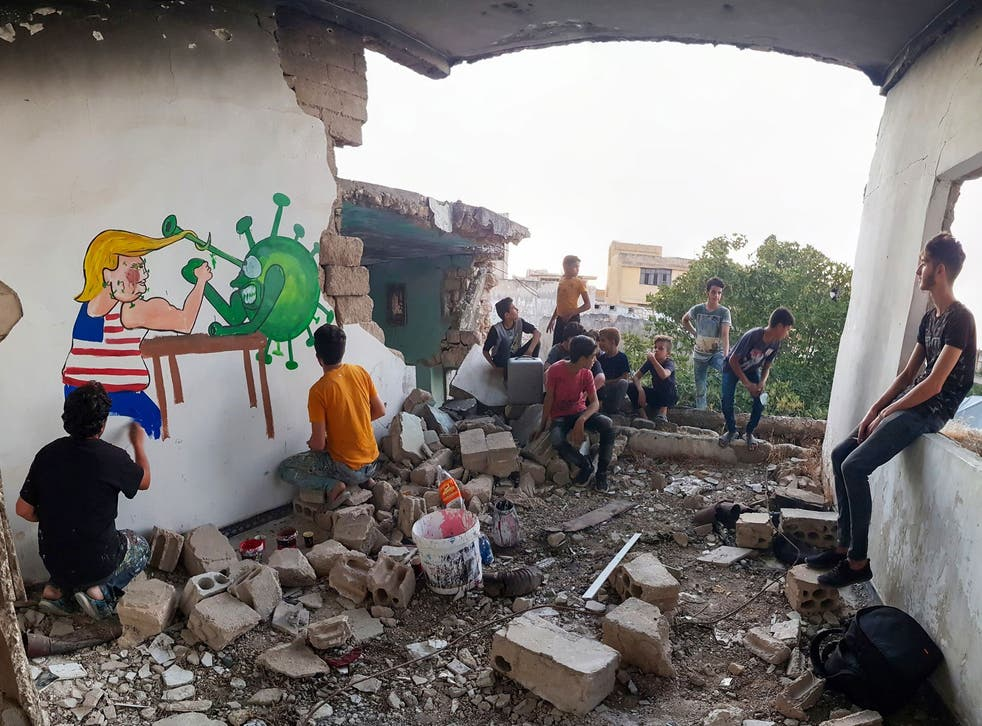 Syrian artists paints a mural in Idlib of Trump fighting coronavirus