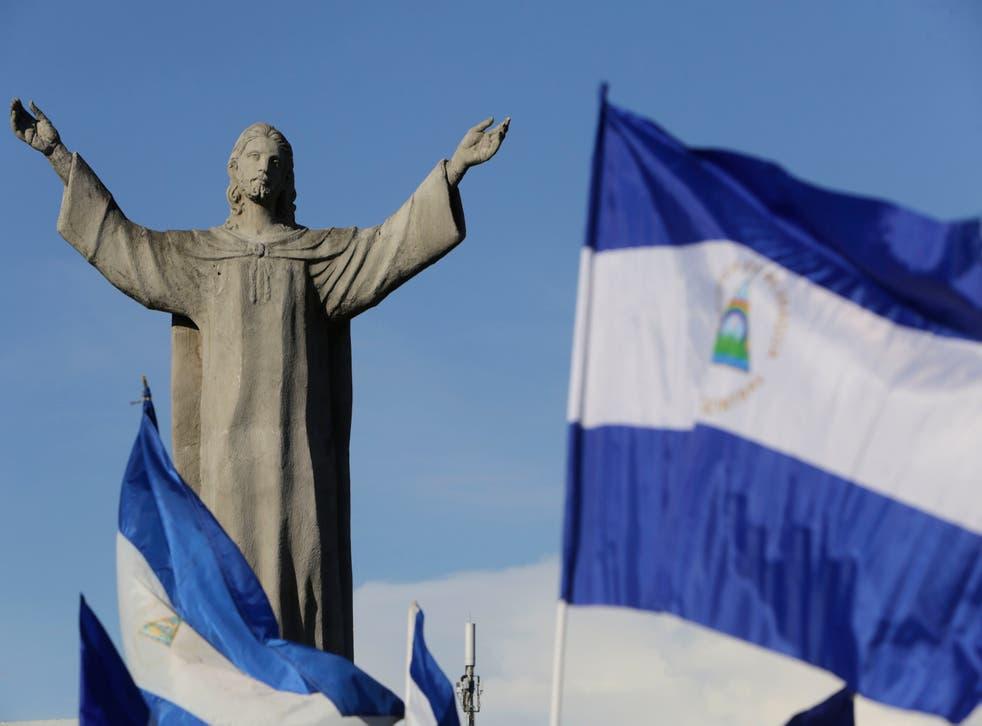 """Banderas nacionales nicaragüenses ondean cerca del monumento """"Cristo Rey"""", en Managua."""