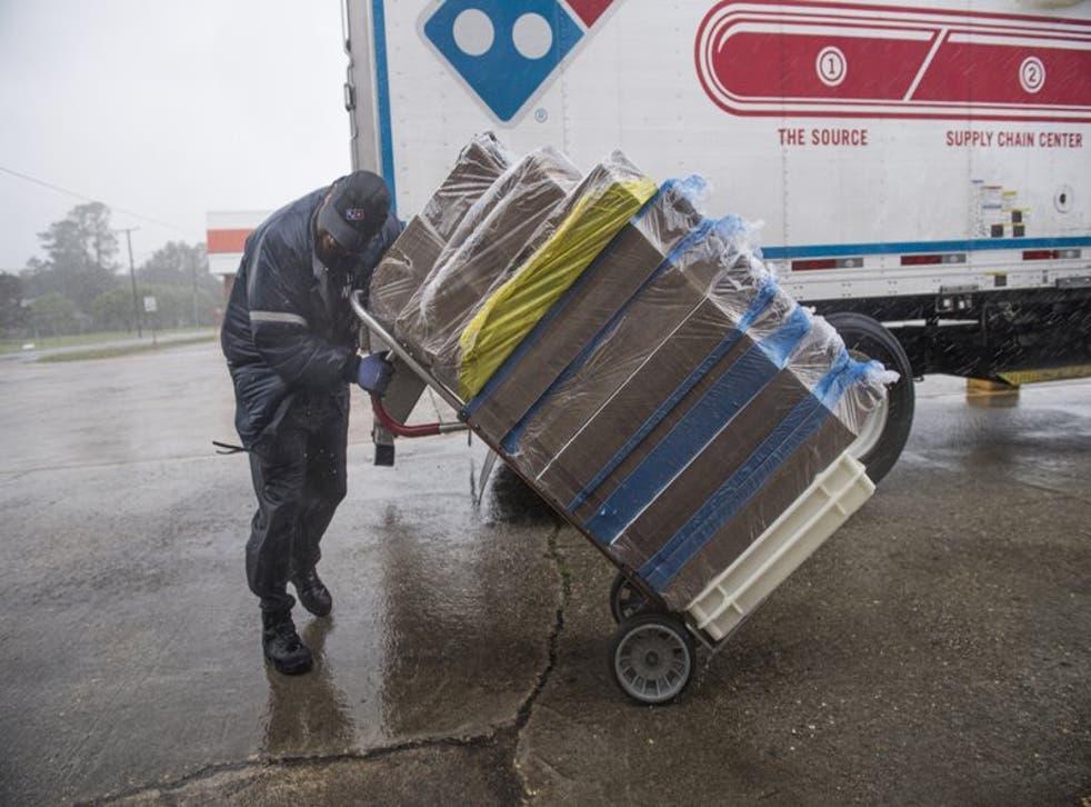 Tran Williams, chofer para Domino's Pizza, pasa trabajos para empujar su carretilla ante la fuerza de los vientos del huracán Delta en Jennings, Luisiana, el viernes, 9 de octubre del 2020. Delta llegó el viernes como una tormenta de Categoría 2 al suroeste del estado. (Chris Granger/The Advocate vía AP)