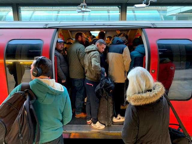 Commuters cram onto the Tube as services are reduced