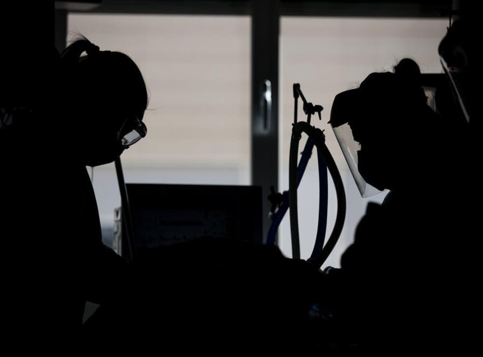 Trabajadores de salud atienden a un paciente de COVID-19 en una unidad de cuidados intensivos en el Hospital Universidad de Torrejón