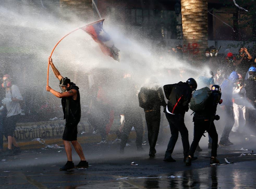 Manifestantes antigubernamentales son reprimidos con cañones de agua de la policía durante una protesta en Santiago de Chile, el viernes 9 de octubre de 2020
