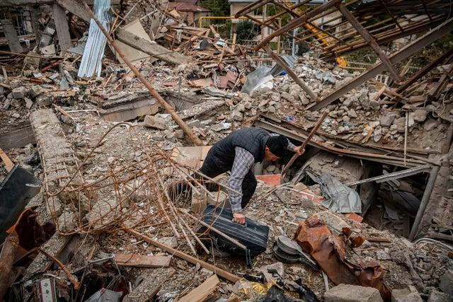 Oficial de policía busca sus pertenencias en los restos de su casa, que se dice fue destruida por el bombardeo azerí