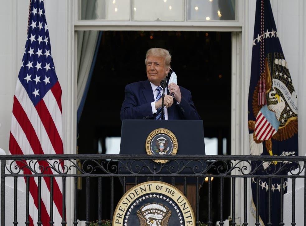 El presidente Donald Trump se retira su mascarilla para pronunciar un discurso desde el balcón del Salón Azul de la Casa Blanca ante partidarios en Washington, el sábado 10 de octubre de 2020. (Foto/Alex Brandon)