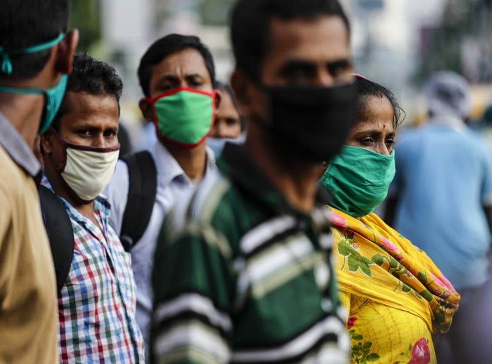 Pasajeros con mascarillas como precaución contra el coronavirus esperan a un autobús en Kolkata, India, el sábado 10 de octubre de 2020. (AP Foto/Bikas Das)