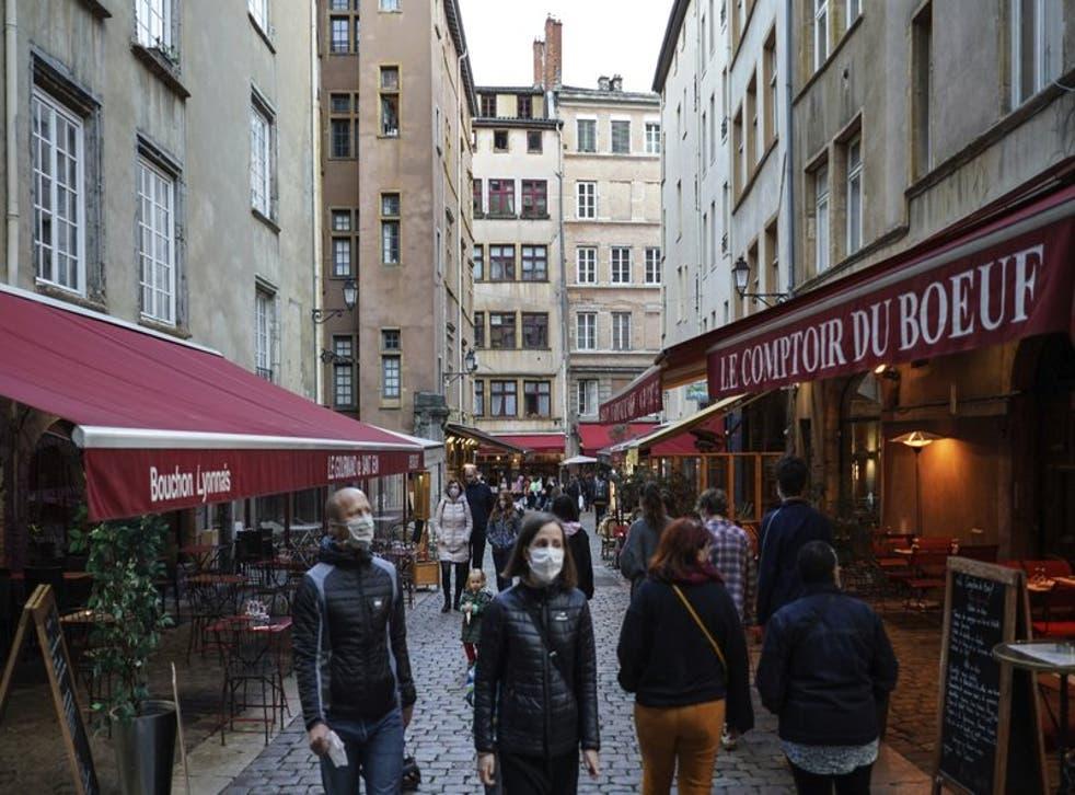 Personas con mascarilla pasan frente a restaurantes en el centro de Lyon, Francia, el sábado 10 de octubre de 2020. (AP Foto/Laurent Cipriani)