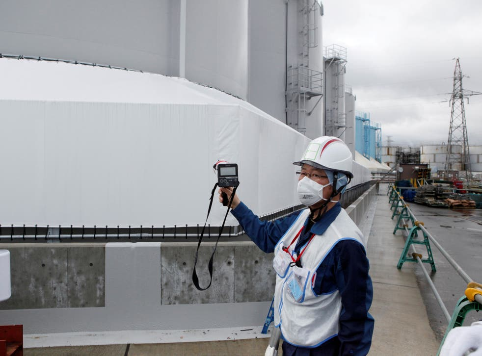 An employee of Tokyo Electric Power Co (TEPCO) uses a geiger counter next to storage tanks for radioactive water at TEPCO's tsunami-crippled Fukushima Daiichi nuclear power plant in Okuma town, Fukushima prefecture, Japan,
