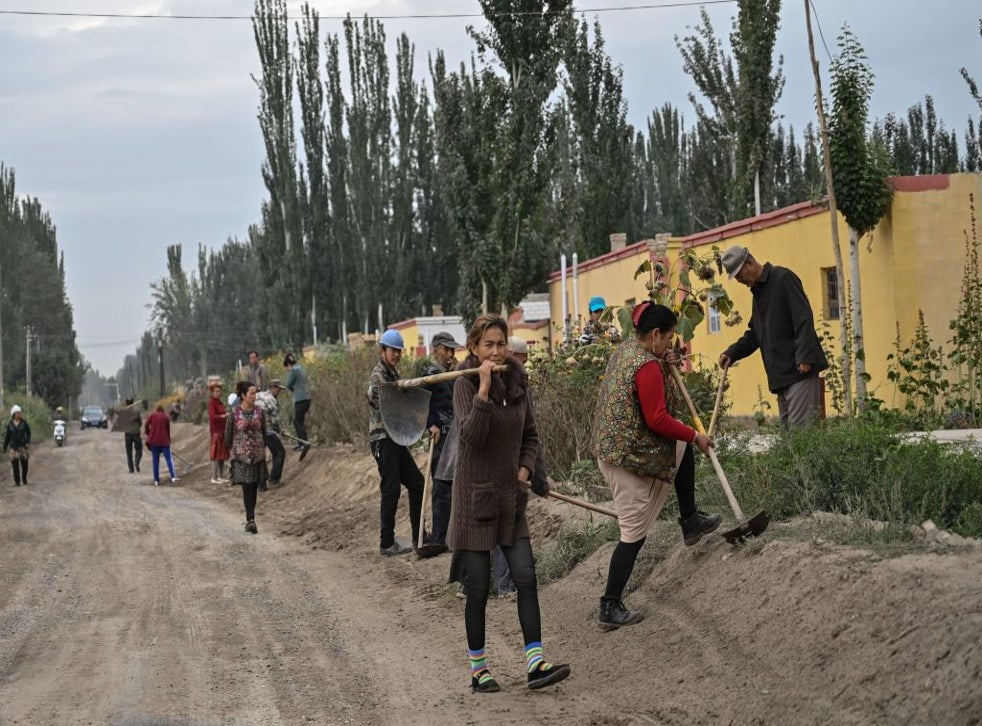 People on a street in a small village where ethnic Uighurs live on the outskirts of Shayar in the region of Xinjiang