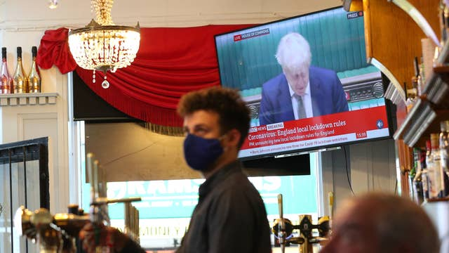 A member of staff pours a drink in the Richmond pub in Liverpool as Prime Minister Boris Johnson reads a statement on television, as parts of the North of England are bracing themselves for the most stringent Tier 3 control